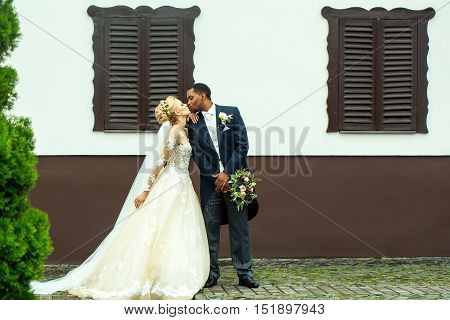 Beautiful bride woman in long elegant white lace dress veil and groom african American man just married couple kiss on wedding day