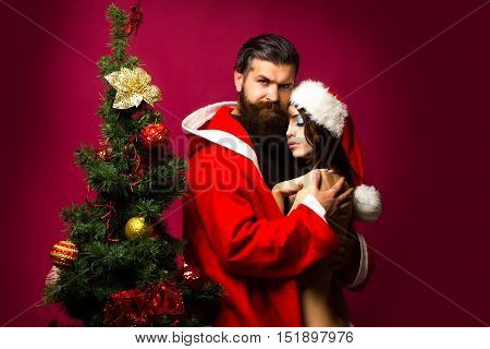 bearded santa claus man with long beard in new year coat with pretty sexy naked girl or woman in hat near decorated Christmas tree on pink background