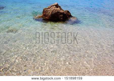 Big stone in blue sea clear rippling shallow water with pebble bottom on sunny summer day