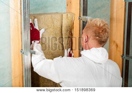 home attic insulation with rock wool working man carpenter