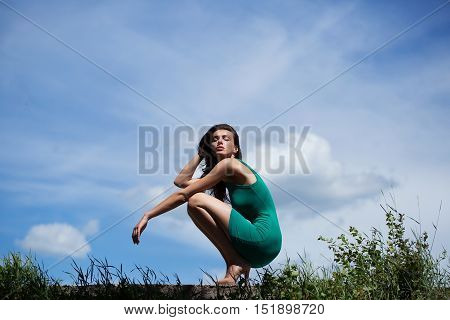 Pretty girl young woman model with slim sexy body in green undershirt poses on summer day on blue sky