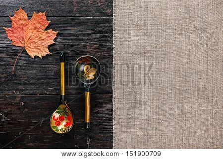 Still life with Russian traditional painted spoons and maple leaf on the half covered table. Flat lay