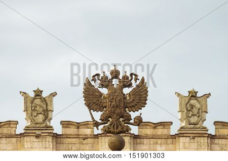 Coat of arms of the Russian Federation. Coat of arms on the background of the parapet of the administrative government building with Soviet symbols. Free copy space at the top.