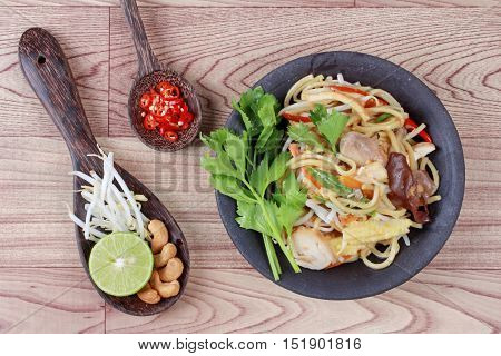 Fried sour sweet  Chinese noodle with tofu,mushroom,red chili,bean sprouts, green lemon,lettuce with side dish as sliced red hot chili pepper ,halved green lemon, bean sprouts and cashew nuts are popular Asia food.