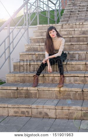 Slim brunette girl with long hair in a green skirt and beige turtleneck sitting on the stone steps and looking into the camera
