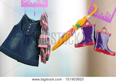 Fashion baby dresses hanging on a hanger. Gray background