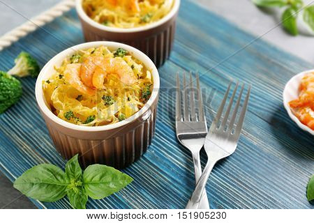 Portions of delicious pasta with shrimps on blue wooden board