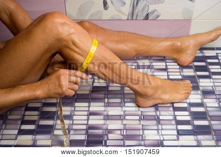 Adult tanned man measures the shin in the bathroom