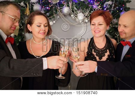 Two happy couple clink glasses with white wine during christmas holiday