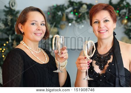 Two happy middle-aged women hold glasses with beads near christmas tree