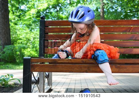 Little girl sits on bench and removes protective pads for roller skating