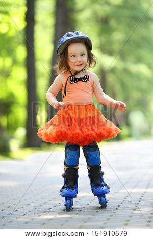 Little girl in skirt and helmet roller-blades and smiles in park at summer day