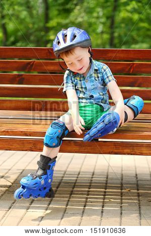 Little boy in roller-blades sits in bench and plays in summer park