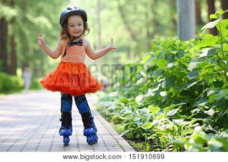 Little happy girl in skirt and helmet roller-blades in garden at summer day