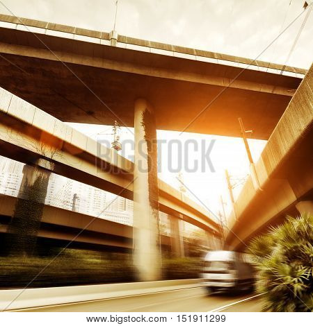 Small truck speeding under industrial bridges. Long exposure burred motion.