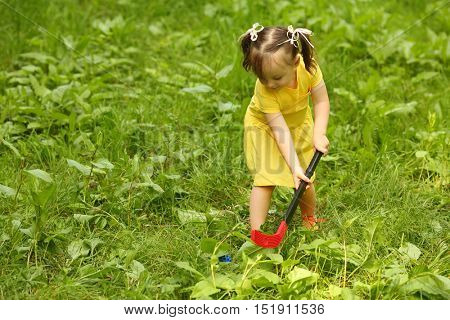 Cute little girl plays with ball and hockey stick on grass in garden