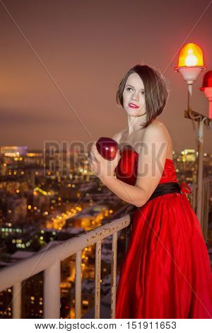 Young woman in red dress stands on roof with obstruction lights behind and holds red apple.