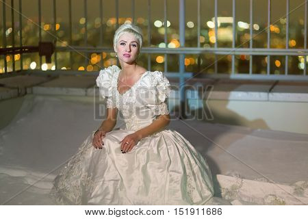 Young woman in white dress sits on snowy high-rise building roof.