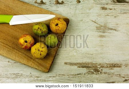 Quince fruit and a knife on an old kitchen board pallet on a wooden table in vintage style copy space. Top flat horizontal view