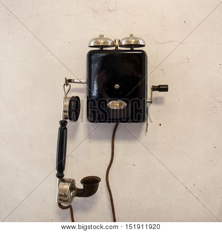 Old dialschool phone by a gray wall