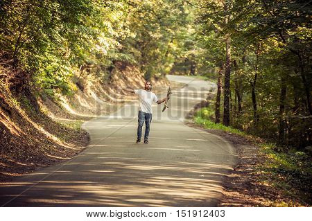 Skateboarder Raising His Hands Up On The Road In The Forest