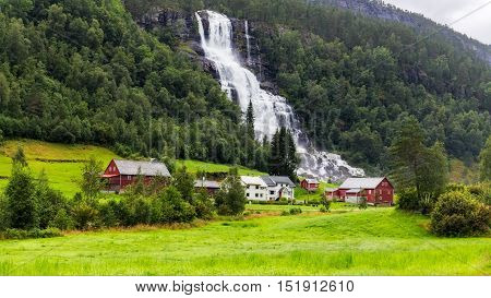 Tvindefossen waterfall and small hamlet in Voss, Norway