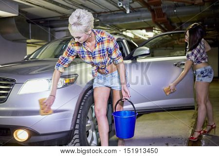 Two young girls in shorts and shirts wash car with sponges at underground parking garage.