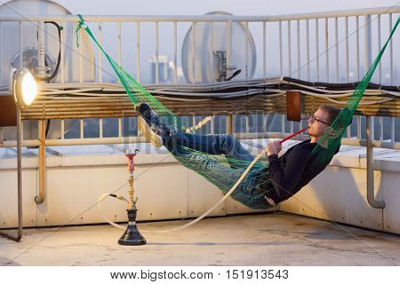 Young man lies in hammock and smokes hookah on highrise roof at sunset.