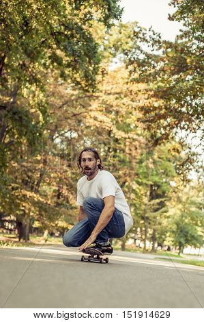Skateboarder Squatting On A Skateboard And Ride Through The Forest