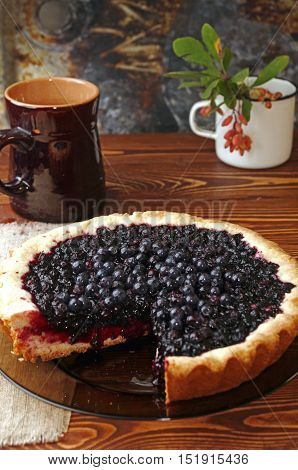 Bilberry cake on wooden table. Rustic style