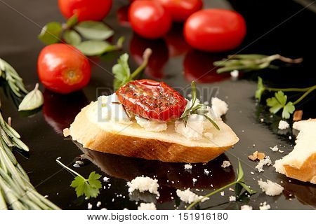 Slice Of Dried Tomato On Bread Piece On Black Background