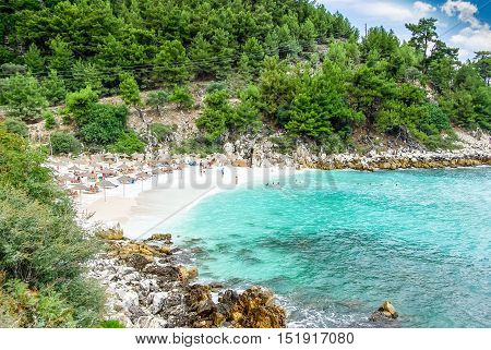 Marble beach (Saliara beach), Thassos Islands, Greece. The most beautiful white beach in Greece. Tourists enjoying a nice day at the beach. Straw umbrellas (straw parasol) and sunbeds on the beach.