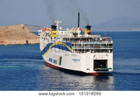 HALKI, GREECE - JULY 19, 2016: Anek Lines ferry boat Prevelis docks at Emborio harbour on the Greek island of Halki. The 142.5mtr vessel was built in Japan in 1980.