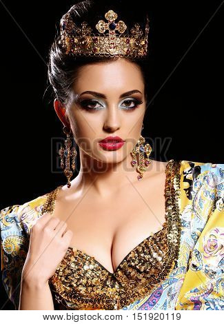 Woman With Dark  Hair In Luxurious Gold Dress With Bijou And Crown,