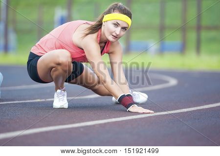 Female Sport Concepts. Young Caucasian Sporstwoman Having Stretching Exercises On Stadium Outdoors.Horizontal Composition