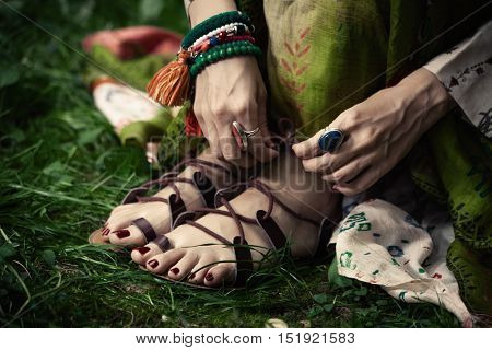 woman feet in boho style strap flat sandals on grass closeup