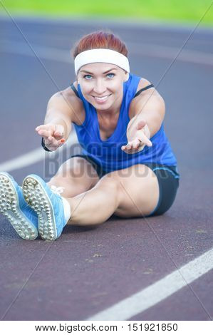 Portrait of Caucasian Female Athlete During Body Stretching Exercises Outdoors. Vertical Shot