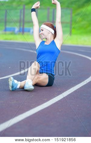 Red Haired Caucasian Sporstwoman Having Stretching Exercises On Sport Venue Outdoors. Vertical Composition