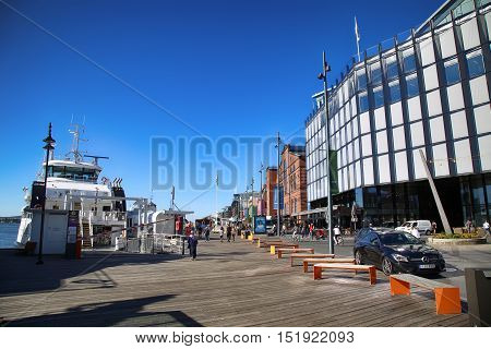 OSLO NORWAY - AUGUST 17 2016: People walking on modern district on street Stranden Aker Brygge district with lux apartments shopping culture and restaurants in Oslo Norway on August 172016.