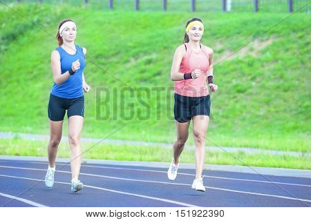 Concepts of Jogging and Healthy Lifestyle. Two Young Caucasian Girlfriends in Athletic Sportswear Having Jogging Exercises Around the Sport Venue. Horizontal Shot