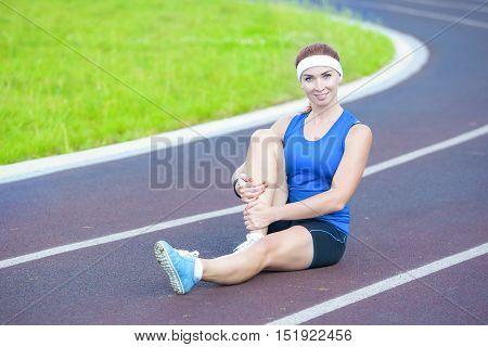 Portrait of Caucasian Female Athlete During Body Stretching Exercises Outdoors. Horizontal Shot