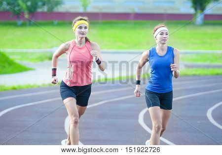 Jogging and Fitness Concepts. Two Young Caucasian Athletes Running Closely to Each Other Outdoors. Horizontal Image Orientation