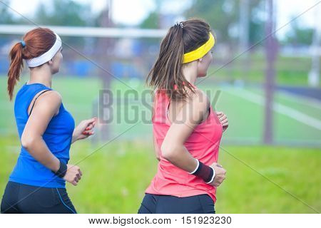 Back View of Two Caucasian Sport Athletes Having Jogging Exercises Together Outdoors. Horizontal Image Composition