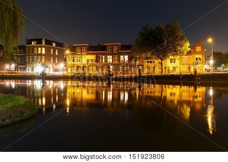 Night canal and typical dutch houses with their reflections in Delft, Holland, Netherlands