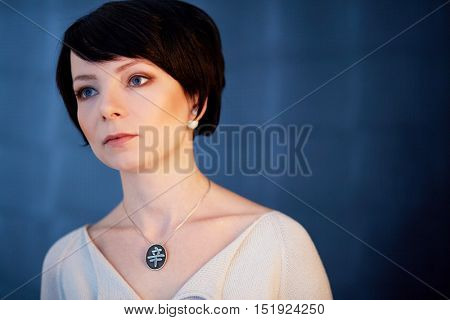 Shoulder portrait of dark-haired woman in white knitted dress.
