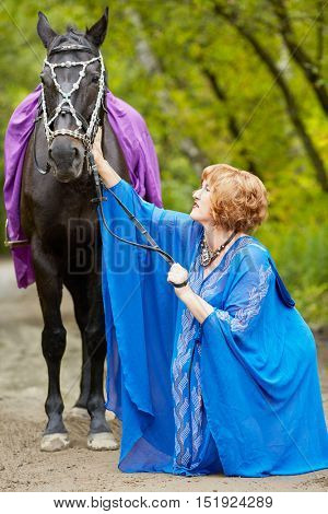 Red-haired smiling woman in blue capote with bay horse in the park.
