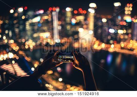 SINGAPORE - SEPTEMBER, 2016 Silhouette of woman using smartphone for taking pictures of city skyline at night