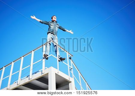 Young man in denim wear stands outstretching arms to sides on metal construction against blue sky.