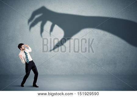 Business person afraid of a big monster claw shadow concept on background
