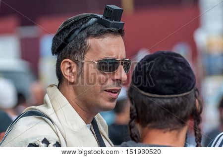 Jewish orthodox hasid wears tefillin, tallit and kippah. Uman, Ukraine - 2 October 2016.